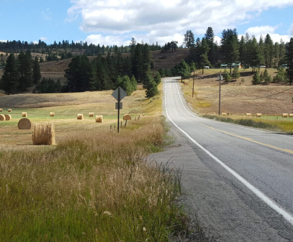 View of Herron Creek Road cutting through farm fields and bales of hay.
